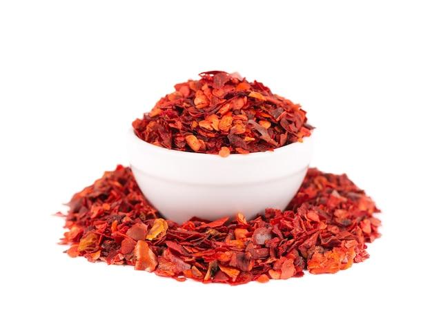 Getrocknete rote chiliflocken in der schüssel, isoliert auf weißem hintergrund. gehackte chili-cayenne-pfeffer. gewürze und kräuter.