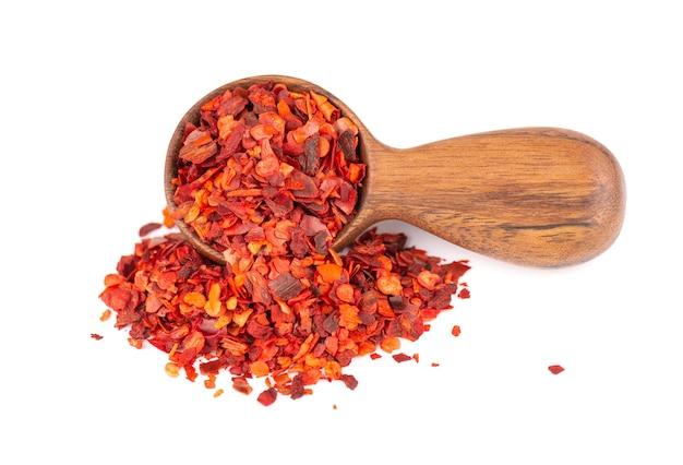 Getrocknete rote chiliflocken in holzlöffel, isoliert auf weißem hintergrund. gehackte chili-cayenne-pfeffer. gewürze und kräuter.
