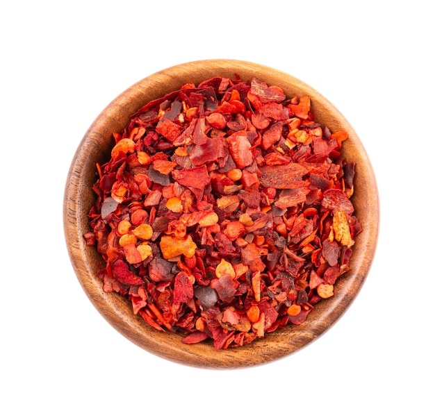 Getrocknete rote chiliflocken in holzschale, isoliert auf weißem hintergrund. gehackte chili-cayenne-pfeffer. gewürze und kräuter. ansicht von oben.