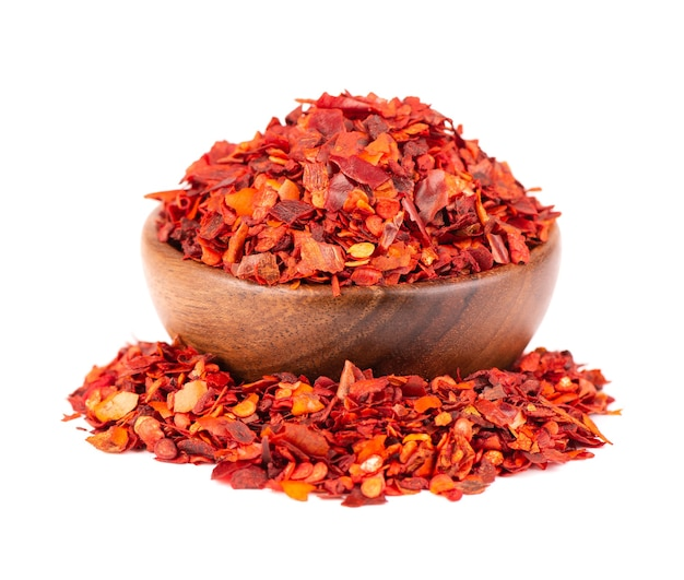 Getrocknete rote chiliflocken in holzschale, isoliert auf weißem hintergrund. gehackte chili-cayenne-pfeffer. gewürze und kräuter.