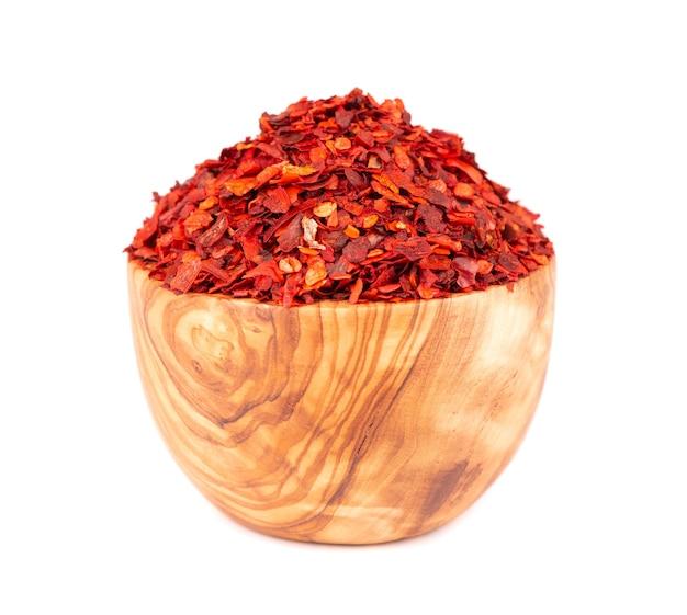 Getrocknete rote chiliflocken in olivenschale, isoliert auf weißem hintergrund. gehackte chili-cayenne-pfeffer. gewürze und kräuter.
