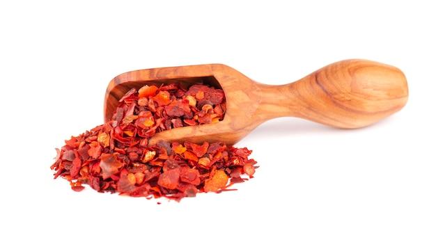 Getrocknete rote chiliflocken in olivenschaufel, isoliert auf weißem hintergrund. gehackte chili-cayenne-pfeffer. gewürze und kräuter.