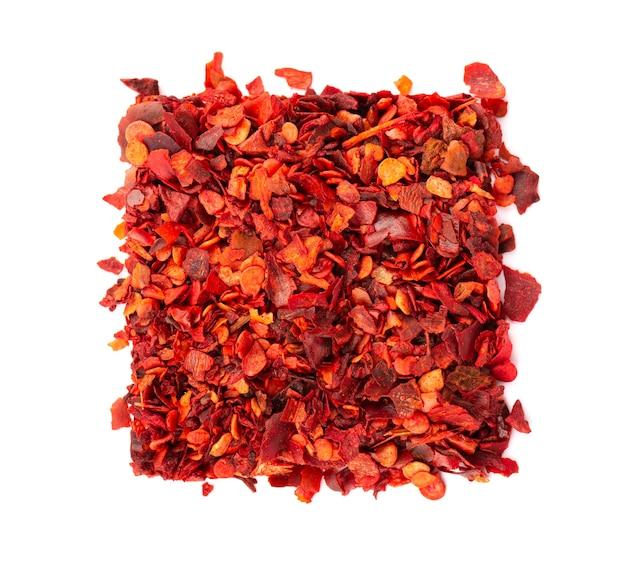 Getrocknete rote chiliflocken mit samen, isoliert auf weißem hintergrund. gehackte chili-cayenne-pfeffer. gewürze und kräuter. ansicht von oben.