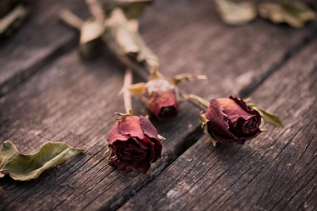Getrocknete rotrose auf hölzernem hintergrund. gebrochenes herz, valentinstagkonzept.