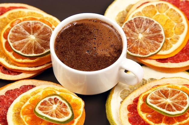 Getrocknete scheiben verschiedener zitrusfrüchte und schwarzer kaffee in einer weißen tasse