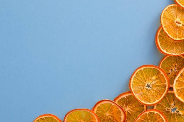 Getrocknete scheibenorangenzitrusfrucht auf hellblauem hintergrund. selbst gemachter natürlicher aromadekor.