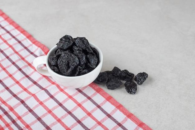 Getrocknete schwarze pflaumen in einer keramikschale.