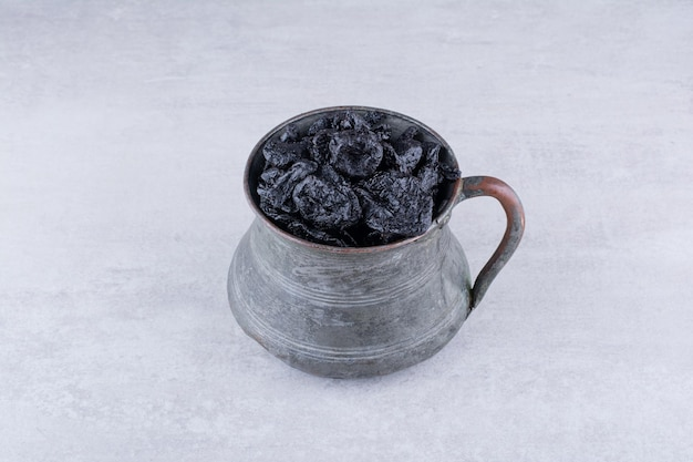 Getrocknete schwarze sultaninen in einer platte auf konkretem hintergrund. foto in hoher qualität