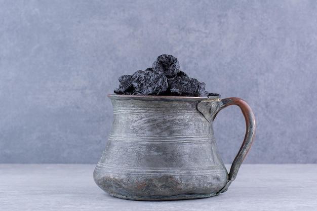 Getrocknete schwarze sultaninen in einer schüssel auf konkretem hintergrund. foto in hoher qualität