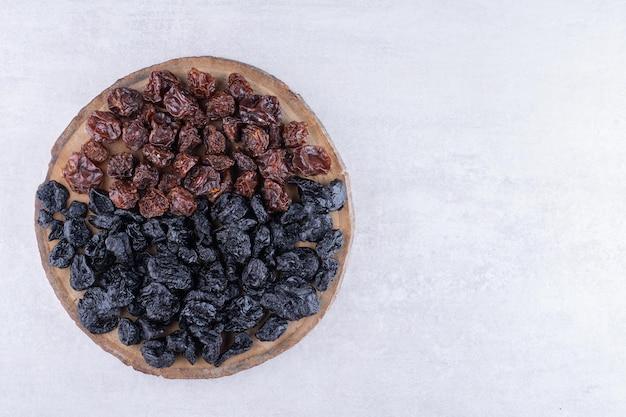 Getrocknete schwarze sultaninen und kirschen auf einer holzplatte. foto in hoher qualität