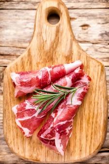 Getrocknete schweinefleischscheiben und rosmarin