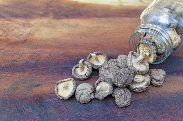 Getrocknete shiitakepilze in einem glasgefäß und getrocknete shiitakepilze auf einem holztisch.