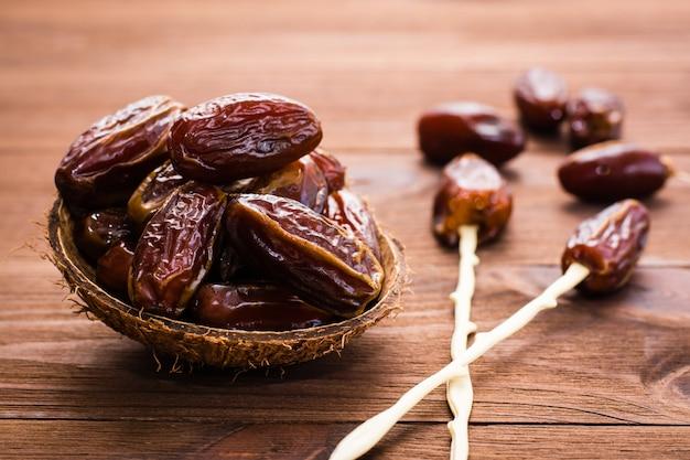 Getrocknete süße datteln obst in der schüssel, stäbchen zum essen auf holz