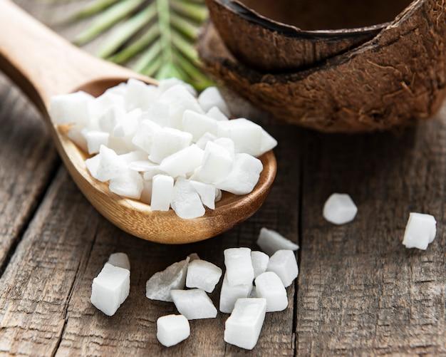 Getrocknete süße kokosnusswürfel im löffel auf holztischhintergrund.