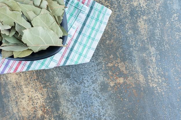 Getrocknete teeblätter in schwarzer schüssel.