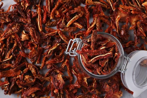 Getrocknete tomaten in einem glas auf dem tisch vor dem hintergrund von verstreuten tomatenchips