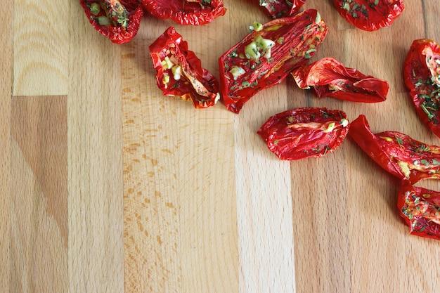 Getrocknete tomaten mit knoblauchscheiben und italienischen kräutern.