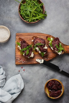 Getrocknete tomatenbruschetta mit quark, knoblauch, rucola, vollkornbrot und olivenöl auf grauem steinhintergrund mit blauer leinenserviette und schwarzem messer. flatlay.