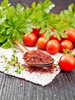 Getrocknete tomatenflocken in einem löffel auf sackleinen, frische kleine tomaten, petersilie und thymian auf dunklem holzbretthintergrund