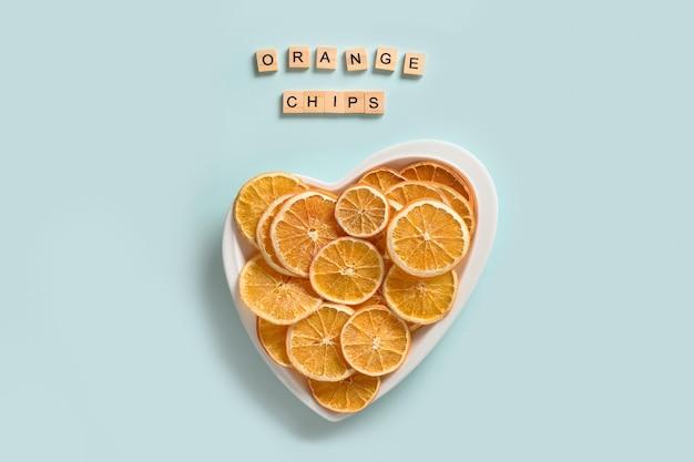 Getrocknete und frische orangenchips auf blau
