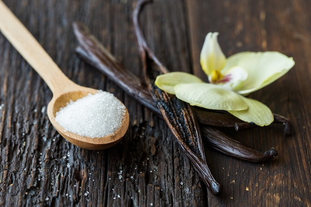 Getrocknete vanillesticks, zucker und vanilleorchidee auf holztisch. nahansicht.