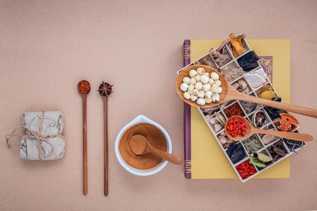 Getrocknete verschiedene chinesische kräuter auf altem hölzernem hintergrund.