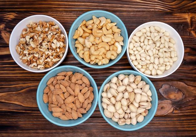 Getrocknete vielzahl von nüssen in eine schüssel auf hölzernem hintergrund. gesundes essen