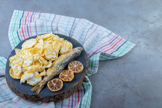 Getrocknete zitrone, fisch und chips auf einem brett auf einem handtuch, auf dem marmorhintergrund.