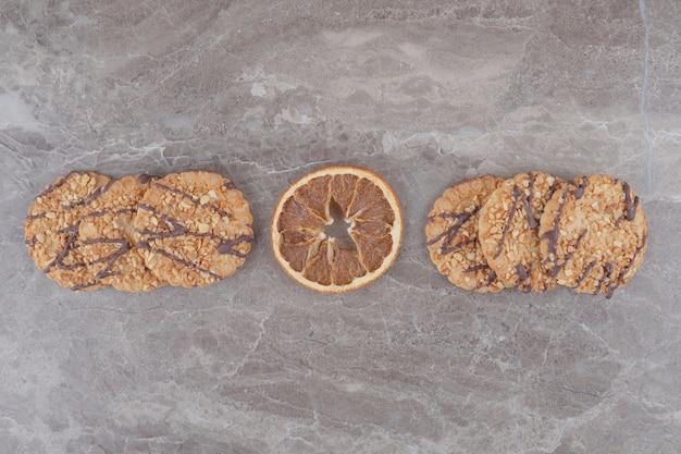 Getrocknete zitronenscheibe und kekse auf marmor