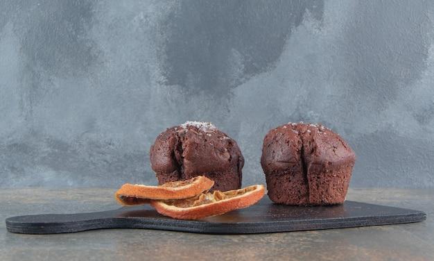 Getrocknete zitronenscheiben und schokoladencupcakes auf holzbrett