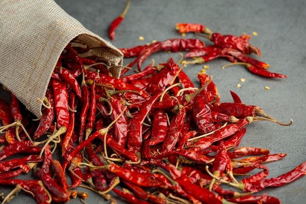 Getrockneter chili-pfeffer, der aus dem sack auf den boden fließt