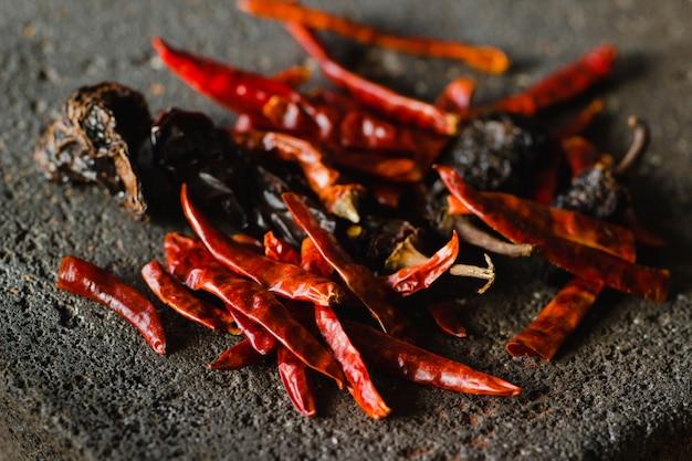 Getrockneter chili-pfeffer-mexikaner, einschließlich sorten von chili-ancho und arbol-chili auf einem traditionellen metate-hintergrund