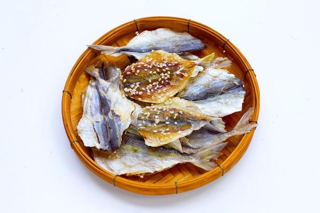 Getrockneter fisch mit sesamsamen im bambuskorb auf weißem hintergrund.