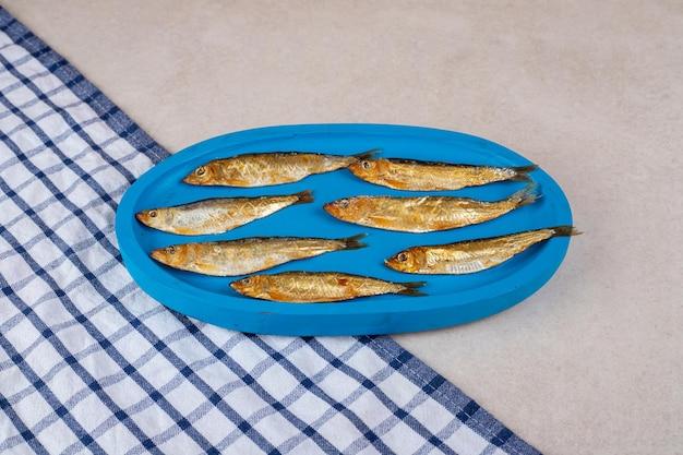 Getrockneter kleiner fisch auf blauem teller