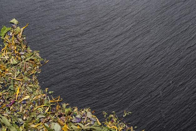 Getrockneter kräutertee auf schwarzem steinhintergrund
