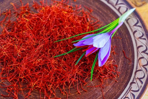 Getrockneter safran mit einer blume in einem gemusterten keramikteller. safrangewürz, das in lebensmitteln und in der traditionellen kräutermedizin verwendet wird