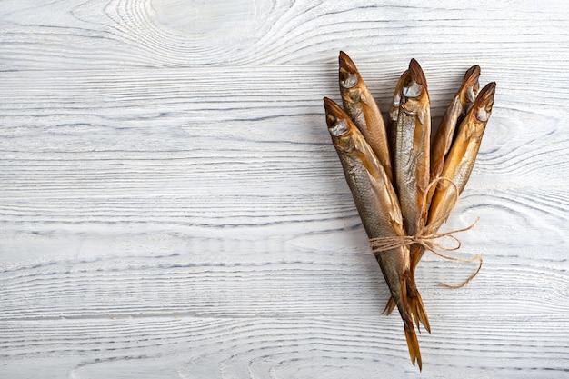 Getrockneter schmelzfisch ist ein idealer snack für bier auf einem hölzernen hintergrund von weißen brettern.