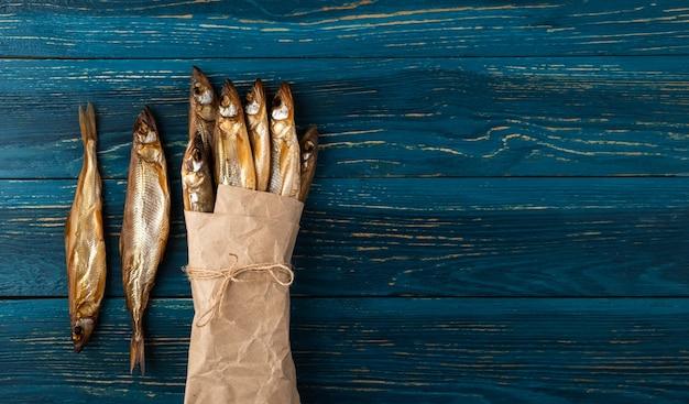 Getrockneter schmelzfisch ist ein idealer snack für bier. eingewickelt in altes bastelpapier auf einem dunkelblauen hölzernen hintergrund.