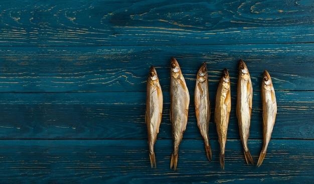 Getrockneter schmelzfisch ist ein idealer snack für bier. es liegt auf einem hölzernen hintergrund aus dunkelblauen brettern.