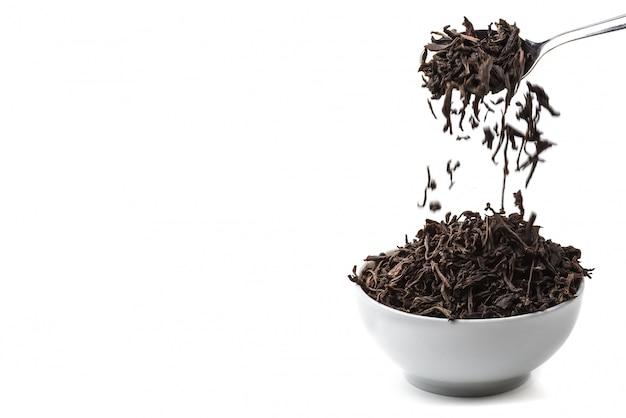 Getrockneter tee gießen aus dem löffel in der keramischen schale über weißer oberfläche.