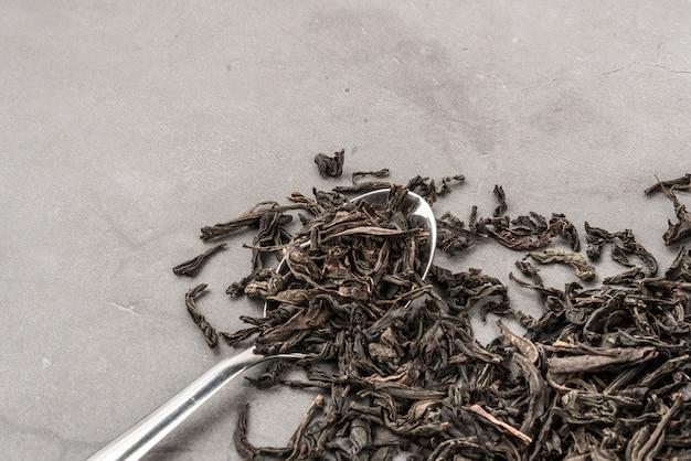 Getrockneter tee und ein löffel auf einem grauen strukturierten hintergrund.
