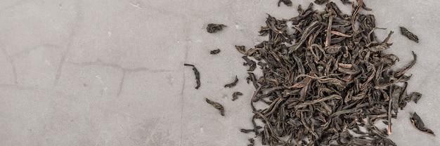 Getrockneter tee wird auf einem grauen strukturierten hintergrund verstreut gegossen.