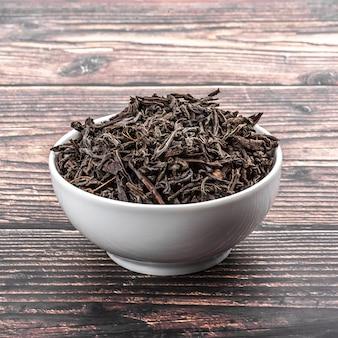 Getrockneter tee wird in eine keramikschale auf einem hölzernen plankentisch gegossen.