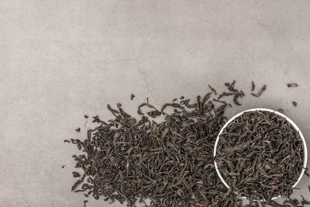 Getrockneter tee wird in eine weiße keramikschale auf einem grau strukturierten raum gegossen. von oben betrachten. layout.
