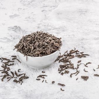 Getrockneter tee wird in eine weiße keramikschale auf einem marmortisch gegossen
