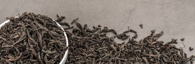 Getrockneter tee wird in eine weiße keramikschale auf einer grauen textur gegossen.