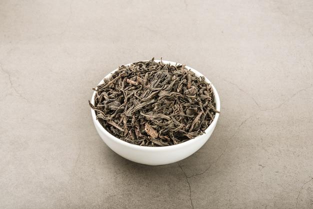 Getrockneter tee wird in eine weiße keramische schale auf einem grauen strukturierten hintergrund gegossen.