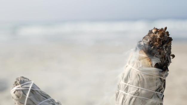 Getrockneter weißer salbei-rauch, trockenes smudge-stick-brennen, soft-fokus-bokeh. aromaverschmierung hautnah am meeresstrand, aromatherapie-meditation durch meerwasserwellen an sandiger küste. yoga, frieden, harmonie und ayurveda