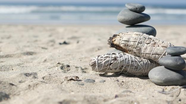 Getrockneter weißer salbeirauch, brennendes räucherstäbchen, aromaverschmierung. felsen balancieren am strand, steine auf dem meer