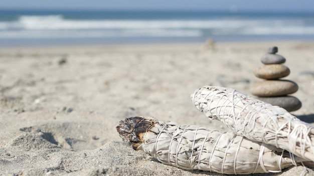 Getrockneter weißer salbeirauch, wischstab brennt in weichem fokus mit bokeh, aromaverschmierung aus nächster nähe. rock balancieren am ozeanstrand, steine stapeln sich durch meerwasserwellen. zen-pyramide aus kieselsteinen am sandstrand